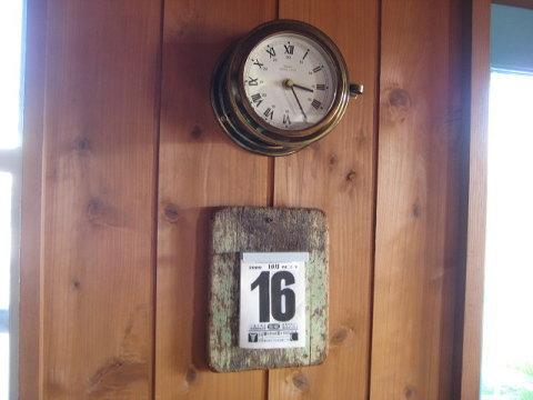 カフェのドア脇にあるアナログの船時計とアナログ以前の日めくりの組み合わせ。