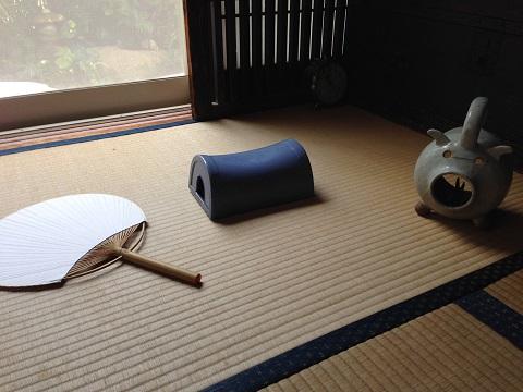 シエスタ用の三点セット。陶枕(中国・清時代)、房州団扇、ブタ蚊取り(横倉悟作)。陶枕はタオルを乗せて使うが硬さが逆に寝すぎないので良い。外の木の鋳物の風鈴が涼を呼ぶ。