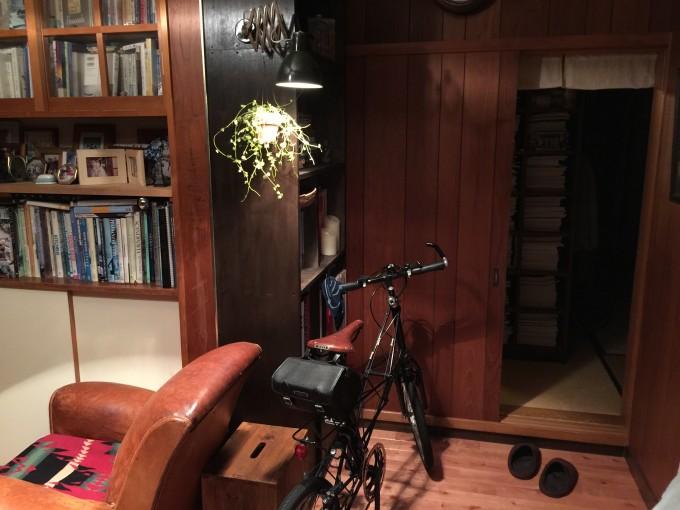 きしむ床の上に新たに桜材のフローリングを重ねて張った。ダークブラウンの本棚を設けビンテージのシザーランプを付けた。