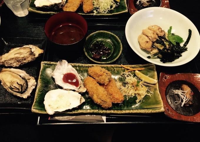 参道にある人気の「牡蠣屋」で昼食。ずらっと並んだワインに釣られて頼んだ牡蠣屋定食。焼き牡蠣、フライ、牡蠣御飯、燻製と牡蠣づくし。